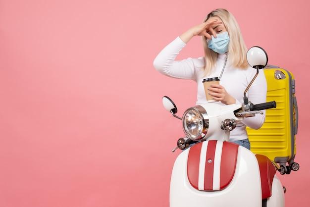 Vue de face insatisfait jeune femme avec masque sur cyclomoteur avec valise jaune tenant une tasse de café