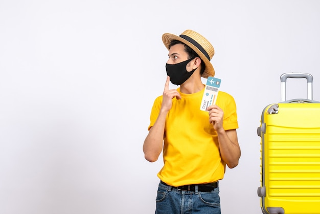 Vue de face intéressé jeune homme avec chapeau de paille debout près de valise jaune tenant un billet de voyage
