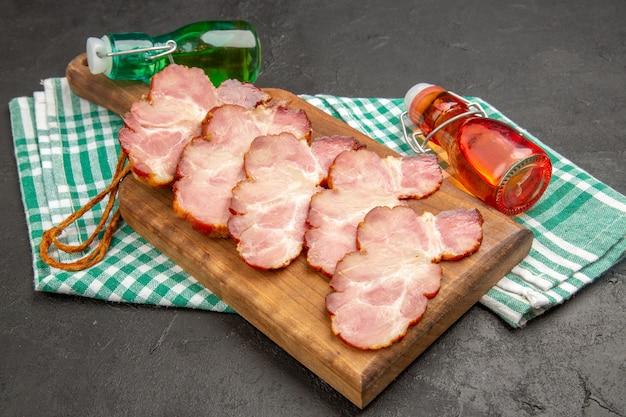 Vue de face de jambon frais tranché sur une photo de porc cru de viande de nourriture de couleur grise