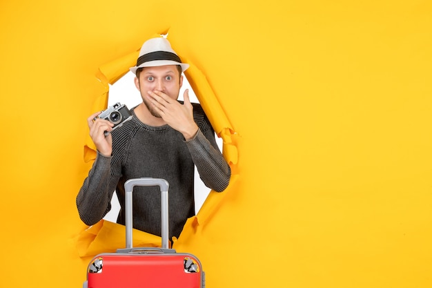 Vue de face d'un jeune adulte surpris tenant un sac et un appareil photo dans un mur jaune déchiré