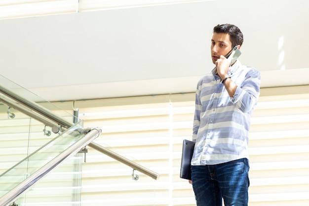 Une vue de face jeune bel homme en chemise rayée parler et discuter des problèmes de travail sur le téléphone pendant la construction d'activités de travail de jour