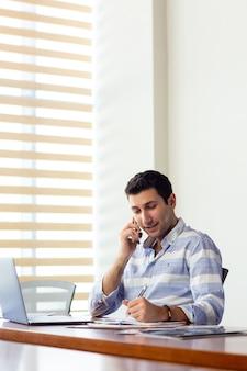 Une vue de face jeune bel homme en chemise rayée travaillant à l'intérieur de la salle de conférence à l'aide de son ordinateur portable argenté à travers des documents parlant au téléphone pendant la construction d'activités de jour