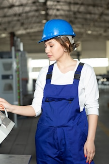 Une vue de face jeune belle dame en bleu costume de construction et casque contrôlant les machines dans le hangar travaillant pendant la construction de l'architecture des bâtiments pendant la journée