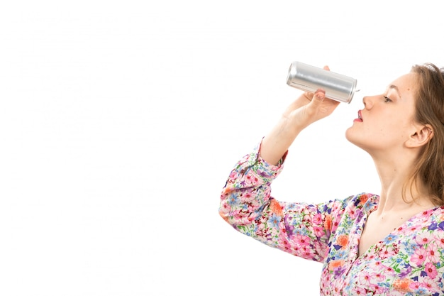 Une vue de face jeune belle dame en chemise conçue de fleurs colorées et jupe bleue tenant l'argent peut boire sur le blanc