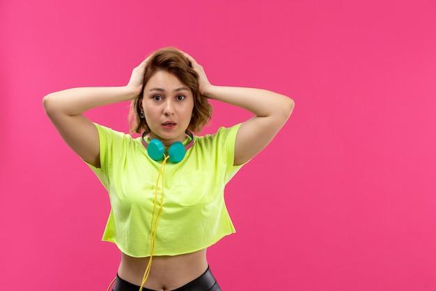 Une vue de face jeune belle dame en chemise de couleur acide pantalon noir avec des écouteurs bleus excité inquiet