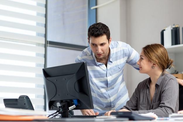 Une vue de face jeune belle dame en chemise grise parler et discuter de quelque chose avec un jeune homme à l'intérieur du bureau pendant la journée