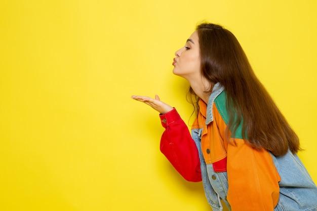 Une vue de face jeune belle dame en chemise rouge et blue-jeans envoi de baisers aériens