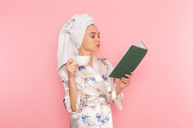 Une vue de face jeune belle dame en peignoir, boire du café et lire un livre