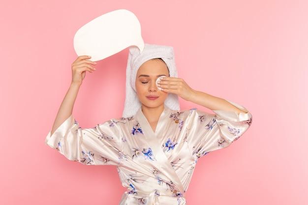 Une vue de face jeune belle dame en peignoir nettoyant tout le maquillage