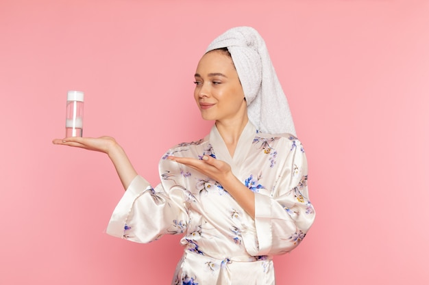 Une vue de face jeune belle dame en peignoir tenant spray nettoyant maquillage