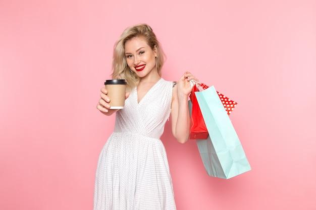Une vue de face jeune belle dame en robe blanche tenant des colis et une tasse de café avec le sourire sur son visage