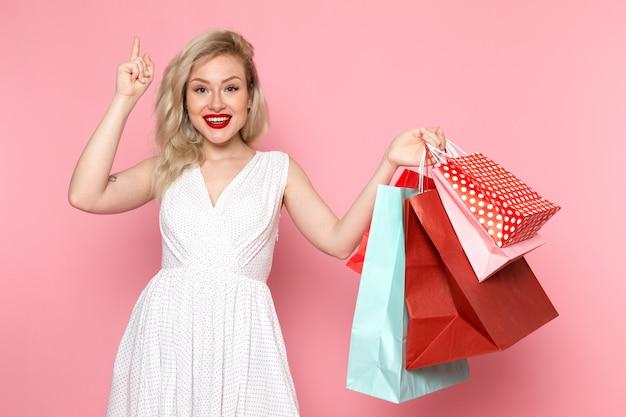 Une vue de face jeune belle dame en robe blanche tenant des paquets commerciaux