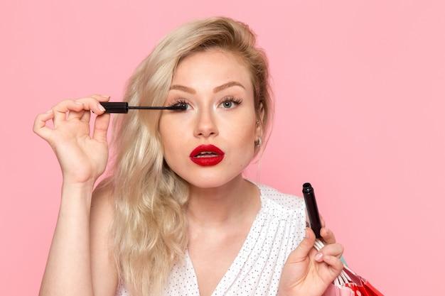 Une vue de face jeune belle dame en robe blanche tenant des paquets de courses et faire du maquillage