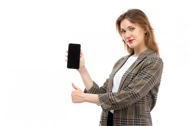 Une vue de face jeune belle dame en t-shirt blanc jeans noirs et manteau tenant montrant smartphone souriant sur le blanc