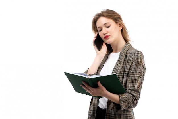 Une vue de face jeune belle dame en t-shirt blanc jeans noirs et manteau tenant un smartphone noir parler et livre vert sur le blanc