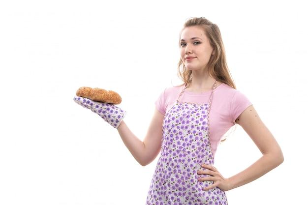 Une vue de face jeune belle femme au foyer en chemise rose cape colorée happy smiling holding boulangeries smiling