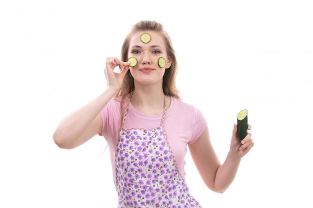 Une vue de face jeune belle femme au foyer en chemise rose cape colorée tenant le concombre