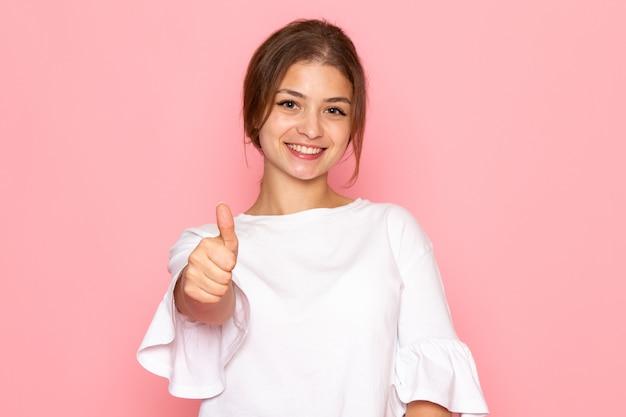 Une vue de face jeune belle femme en chemise blanche posant avec une expression heureuse