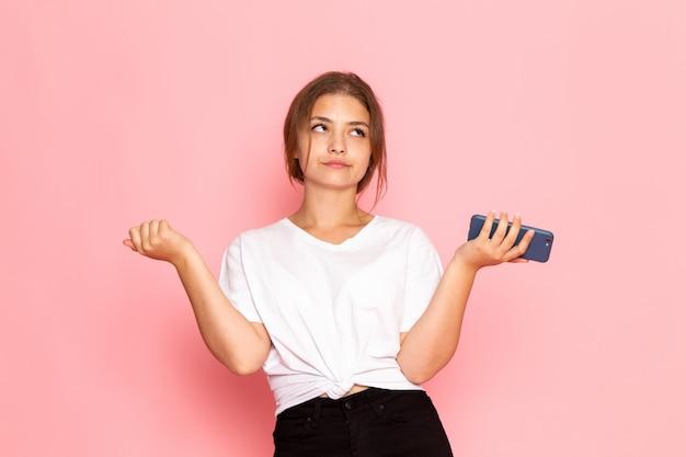 Une vue de face jeune belle femme en chemise blanche tenant un téléphone