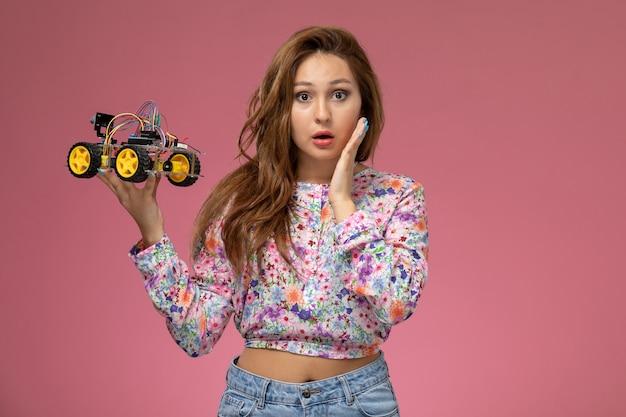 Vue de face jeune belle femme en chemise conçue de fleurs et blue-jeans tenant une voiture jouet sur le fond rose