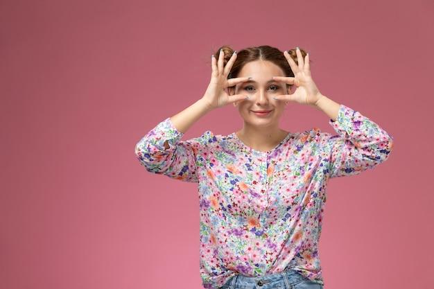 Vue de face jeune belle femme en chemise conçue de fleurs et jeans bleus souriant montrant ses yeux sur le mur rose