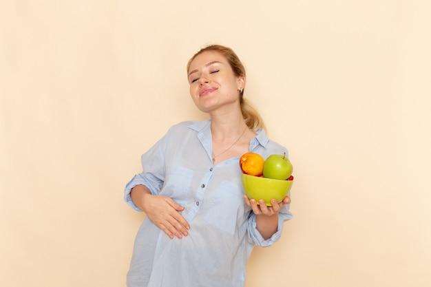 Vue de face jeune belle femme en chemise tenant la plaque avec des fruits et souriant posant sur le mur crème fruits modèle femme pose dame