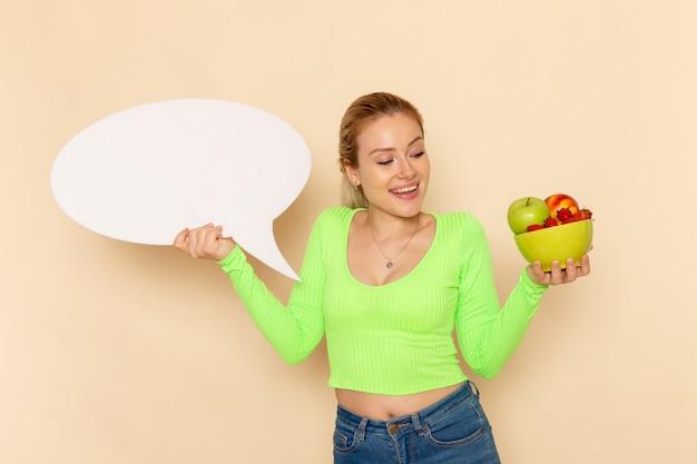 Vue de face jeune belle femme en chemise verte tenant une assiette pleine de fruits avec un grand panneau blanc sur mur crème fruit modèle femme