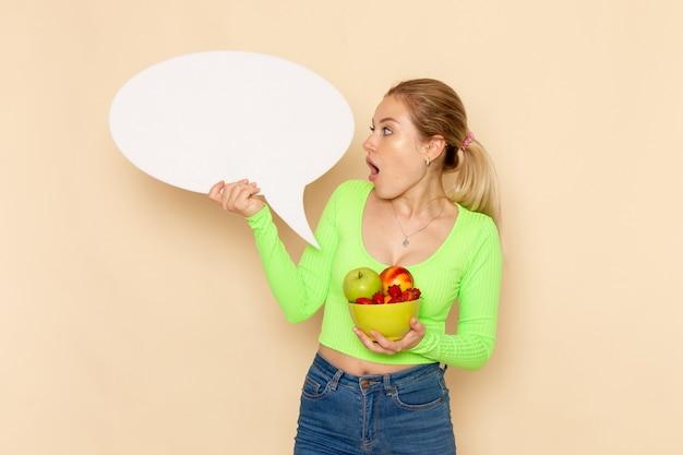 Vue de face jeune belle femme en chemise verte tenant une assiette pleine de fruits et signe blanc sur mur crème fruits modèle femme alimentaire