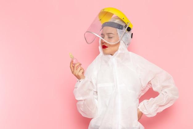 Vue de face jeune belle femme en costume blanc spécial portant un casque de protection holding spray sur l'espace rose costume spécial fille femme
