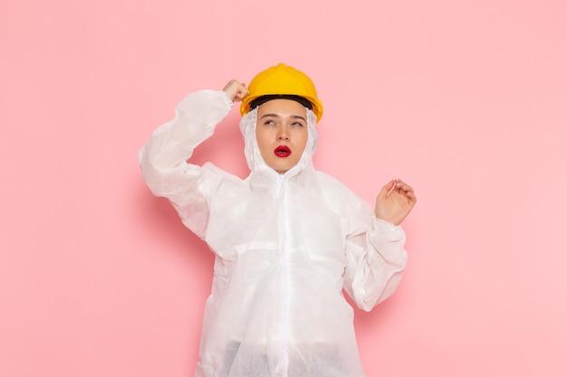 Vue de face jeune belle femme en costume blanc spécial portant un casque de protection posant et en pensant à la chimie de la femme combinaison spatiale rose