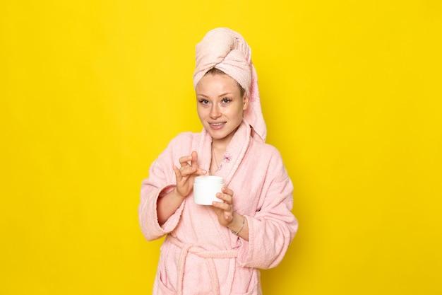 Une vue de face jeune belle femme en peignoir rose à l'aide de crème pour le visage