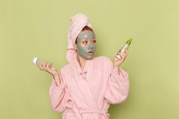 Une vue de face jeune belle femme en peignoir rose avec masque facial tenant des flacons de pulvérisation