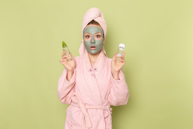 Une vue de face jeune belle femme en peignoir rose avec masque facial tenant des flacons