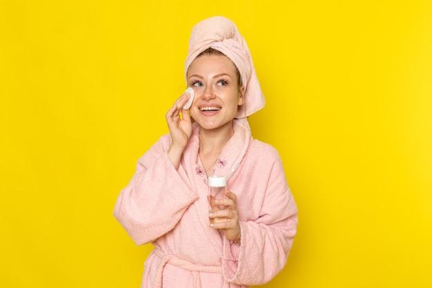 Une vue de face jeune belle femme en peignoir rose nettoyer tout le maquillage avec un nettoyant