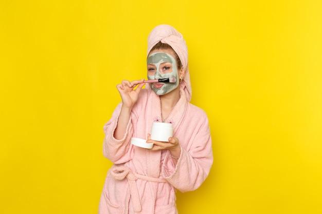 Une vue de face jeune belle femme en peignoir rose tenant la crème pour le visage peut et brosse
