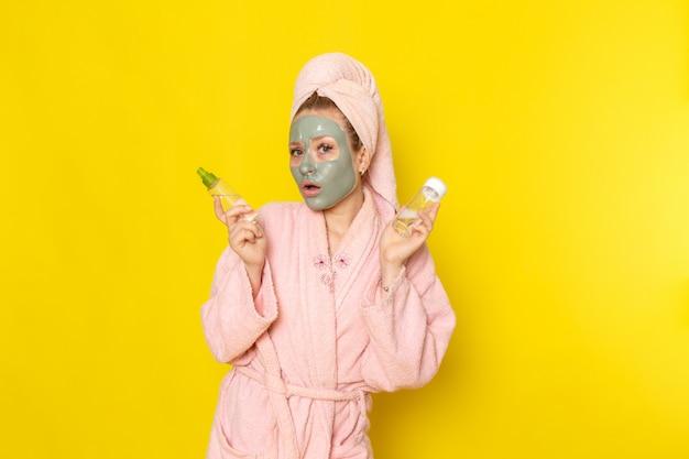 Une vue de face jeune belle femme en peignoir rose tenant des flacons de pulvérisation