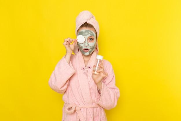 Une vue de face jeune belle femme en peignoir rose tenant spray nettoyant maquillage