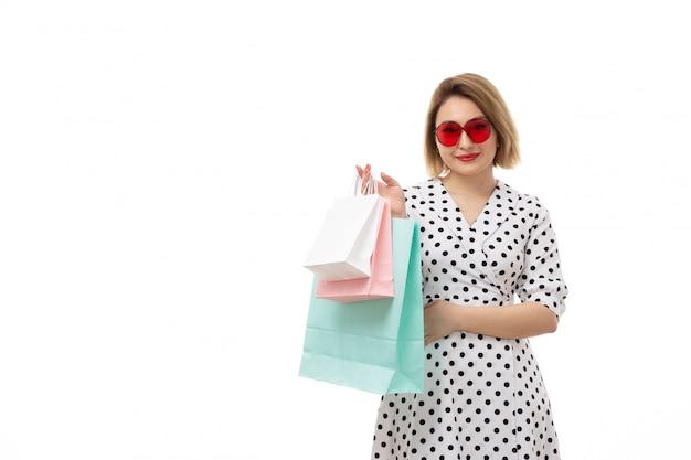Une vue de face jeune belle femme en robe à pois en noir et blanc en lunettes de soleil rouges tenant des colis posant