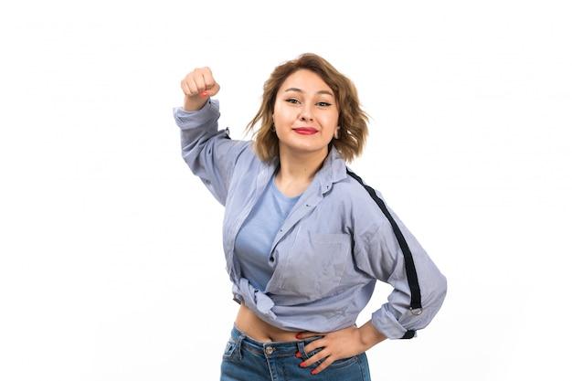 Une vue de face jeune belle fille en chemise bleue et blue jeans smiling prépare à frapper sur le blanc