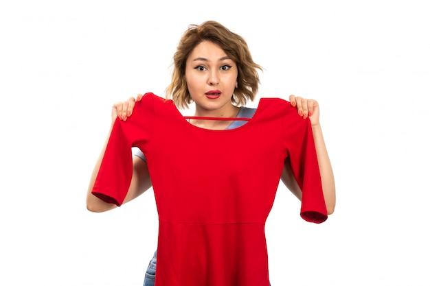 Une vue de face jeune belle fille en chemise bleue et jeans bleu mesurant la robe rouge sur le blanc