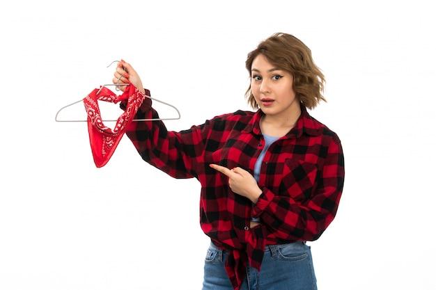 Une vue de face jeune belle fille en chemise à carreaux rouge-noir et blue jeans holding accrocher sur le blanc