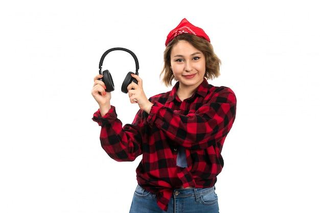 Une vue de face jeune belle fille en chemise à carreaux rouge-noir et blue-jeans tenant des écouteurs noirs souriant sur le blanc
