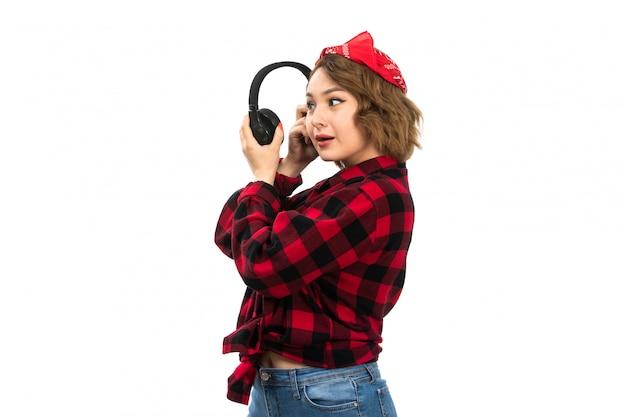 Une vue de face jeune belle fille en chemise à carreaux rouge-noir et blue-jeans tenant des écouteurs noirs souriant à l'écoute sur le blanc
