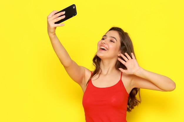 Une vue de face jeune belle fille en chemise rouge et jean bleu prenant un selfie avec sourire