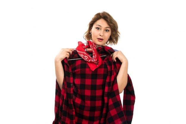 Une vue de face jeune belle fille en t-shirt bleu et jean bleu tenant une chemise à carreaux rouge-noir sur le blanc