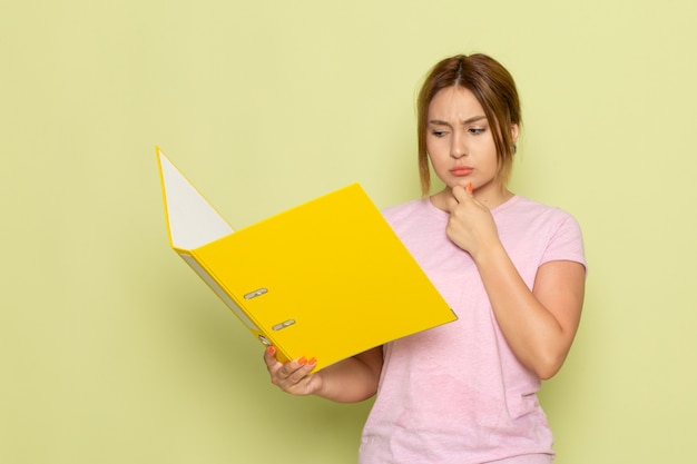 Une vue de face jeune belle fille en t-shirt rose jeans bleu lecture fichier jaune avec expression de la pensée sur le vert