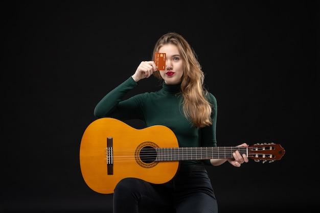 Vue de face d'une jeune belle musicienne émotionnelle drôle tenant une guitare et montrant une carte bancaire dans l'obscurité