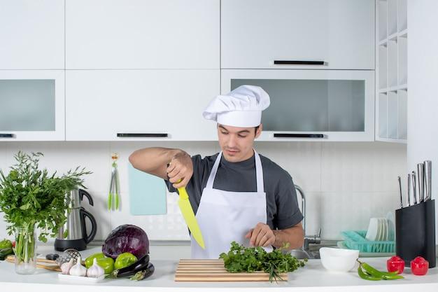 Vue de face jeune chef en chapeau de cuisinier et tablier de coupe de légumes verts