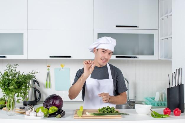 Vue de face jeune chef en chapeau de cuisinier