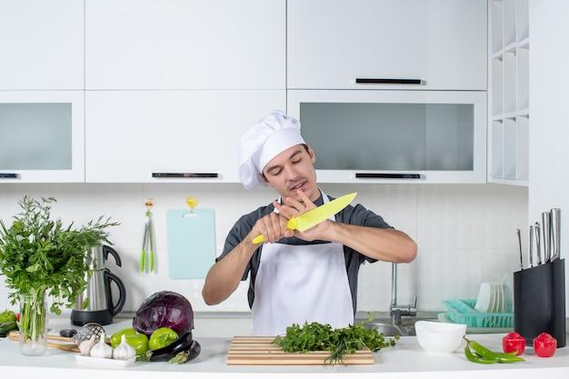 Vue de face jeune chef nettoyant son couteau
